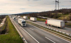 Auto, Trucking, Transportation Convoys Or Caravans Of Transportation Trucks Passing On A Highway
