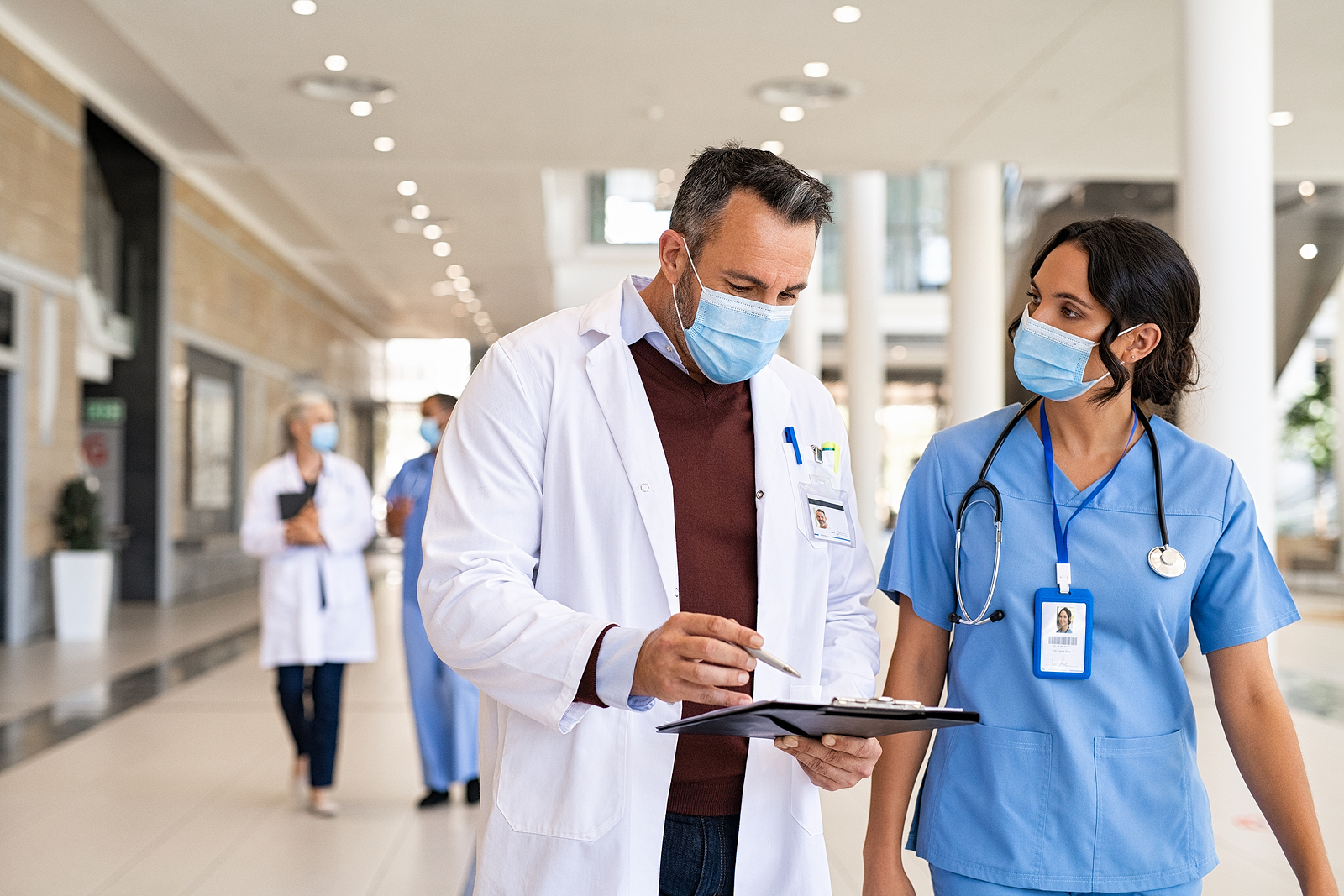 General practitioner and nurse wearing surgical face mask in hospital hallway.